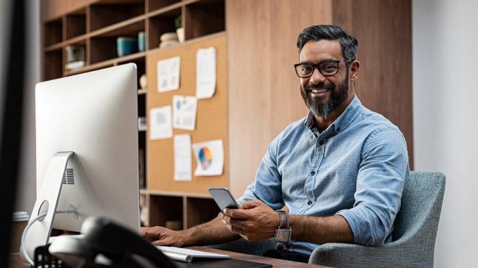 Man mit blauen Hemd und Brille sitzt mit Handy in der Hand vor dem PC und lächelt in die Kamera.