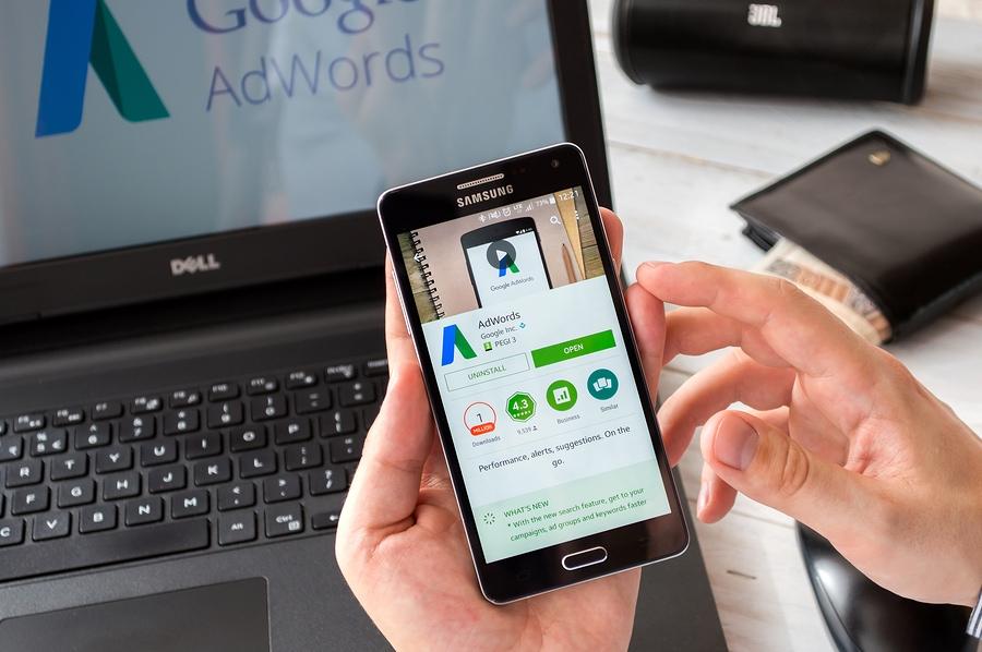 Geschäftsmann bereitet vor sich, Google Adwords-Anwendung auf Samsung A5 zu installieren. Google Adwords ist ein Werbesystem, mit dem gesponserte Links in den Google-Suchergebnissen angezeigt werden können.