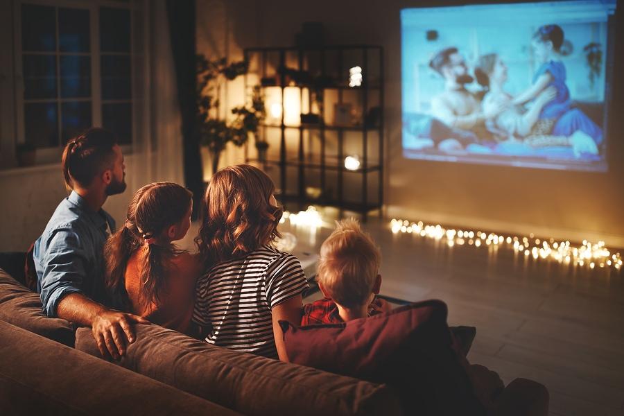 familie mutter vater und kinder schauen projektor, fernsehen, filme mit popcorn am abend zu hause