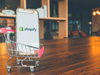 Handy mit Shopify-App auf dem Bildschirm im Einkaufswagen auf Holztisch.