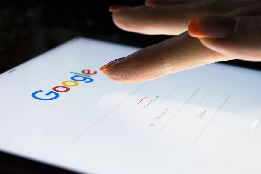 Die Hand einer Frau berührt Bildschirm auf Tablet-Computer iPad Pro nachts für das Suchen auf Google-Suchmaschine. Google ist die beliebteste Internet-Suchmaschine der Welt.