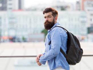 Rucksack für Reisen und Stadtleben. Hipster trägt Rucksack im lässigen Stil auf urbanem Outdoor. Bärtiger Mann, der mit Rucksack in den Sommerferien reist. Rucksack auf Rucksackreise mitnehmen.