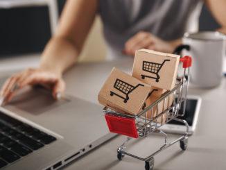 Online Einkaufen . E-Commerce- und Lieferservice-Konzept: Papierkartons mit einem Wagen- oder Wagenlogo auf einer Laptoptastatur zeigen Kunden, wie sie über das Internet bei Einzelhändlern bestellen.