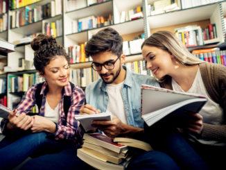 Porträt eines jungen frohen männlichen Studenten, der auf einem Bibliotheksschreibtisch lernt, auf dem zwei Studentinnen in einem Hintergrund studieren. eines Übersetzungen für eines PronomenHäufigkeit one eine, einer, eines, man, eins, nach dem anderen one thing eines, eins