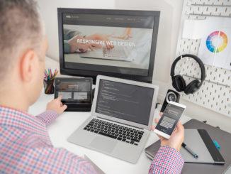 Ein Mann im Hemd designed eine Website und bedient Smartphone und Laptop gleichzeitig