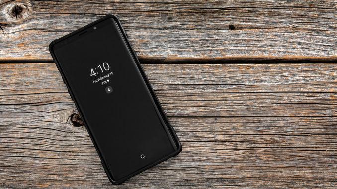 Studioaufnahme des Samsung Galaxy Note 9-Smartphones auf einem hölzernen Hintergrund, entwickelt und vermarktet von Samsung Electronics.