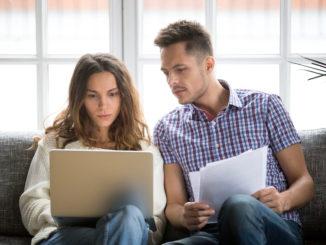 Eine junge Frau und ein junger Mann sitzen auf der Couch und schauen auf ein Notebook