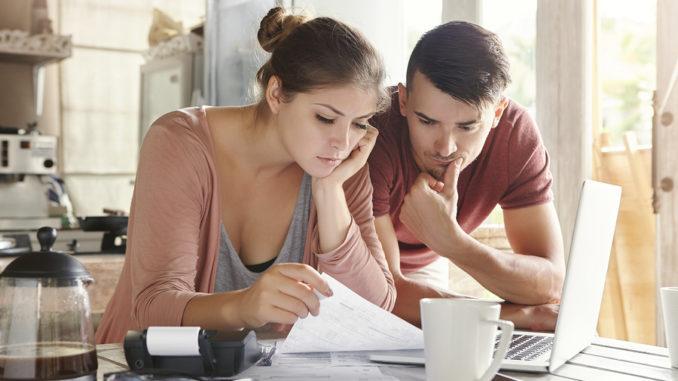 Eine junge Frau und ein junger Mann sitzen vor dem Notebook und führen ein digitales Haushaltsbuch