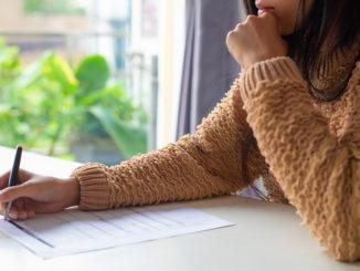Eine junge Frau füllt eine Gewerbeanmeldung aus.