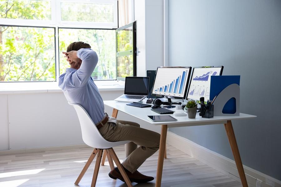 Ein Geschäftsmann sitzt an seinem Schreibtisch. Schreibtisch und Stuhl sind weiß.