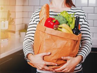 Eine junge Frau hält eine große Tüte mit Lebensmitteln wie frischem Gemüse in der Hand