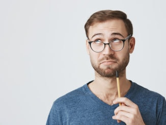 Die horizontale Aufnahme eines nachdenklichen Universitätsprofessors mit Bart trägt eine Brille und Freizeitkleidung, hat einen klugen Ausdruck, schaut nachdenklich zur Seite, hält einen Stift auf seinem Kinn, isoliert vor grauem Hintergrund mit Kopierraum. Gesichtsausdruck
