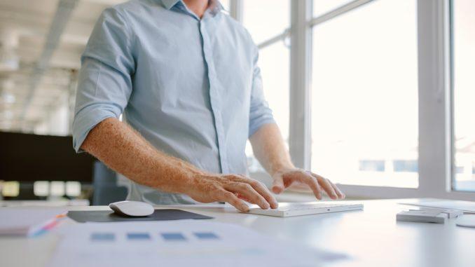 Ein junger Mann in blauem Hemd arbeitet im Stehen am Computer.