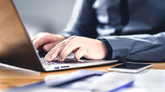 Mann, der mit Laptop schreibt. Kluger Hipster mit Finanz-, Markt- und Geschäftskenntnissen. Freiberufliche Arbeit mit digitalen Geräten. Telefon auf Tisch und Schreibtisch. Geschäftsmann mit Notebook im Büro