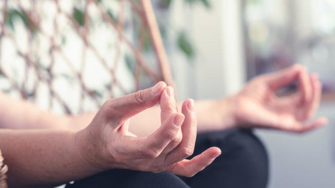 Ältere Frau, die Yoga zu Hause macht. Ältere Frau Hände in Yoga-Position. Älterer Rentner, der zu Hause Yoga macht. Frau Senior in der Yoga-Position im Schaukelstuhl. Yoga. Meditation. Ältere Frau.