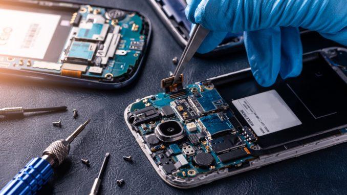 Zerlegtes Smartphone auf dem Tisch wird repariert