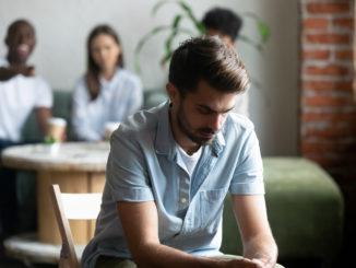 Ein junger Mann sitzt alleine in der Aula, weil er gemobbt wird