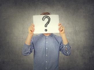 Ein junger Mann in blauem Hemd hält einen Zettel mit einem Fragezeichen hoch
