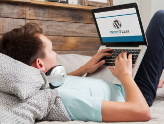 WordPress-Markenlogo auf dem Computerbildschirm. Mann, der auf der Tastatur tippt. WordPress ist ein kostenloses Open-Source-Blogging-Tool und ein Content-Management-System (CMS).