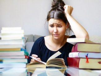 Eine junge Frau sitzt vor Ihren Schulbüchern