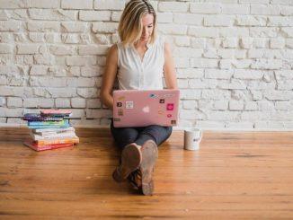 Eine Influencerin sitzt auf dem Boden mit ihrem Notebook auf dem Schoß