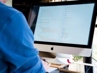 Ein IT-Systemkaufmann sitzt vor dem PC und programmiert