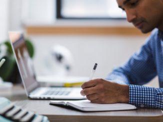 Geschäftsmann sitzt mit Notizblock vor Laptop