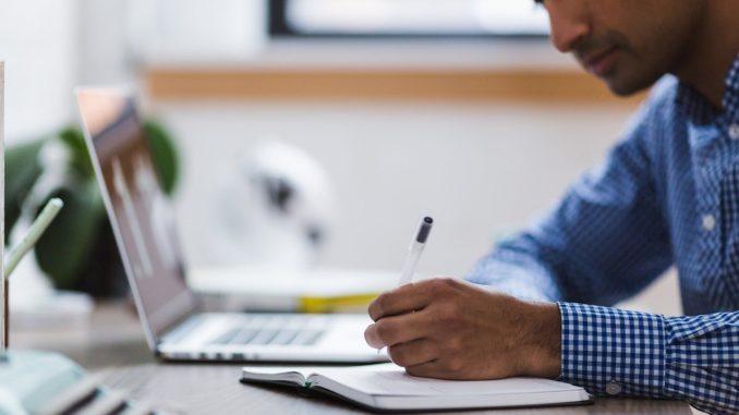Business-Mann sitzt vorm Laptop und macht Notizen