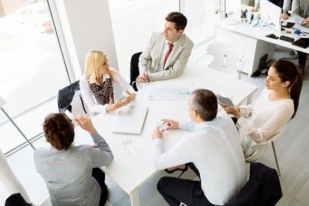 Büroleute sitzen zusammen am Besprechungstisch