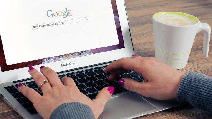 Frau bedient ein Macbook und ist auf Google