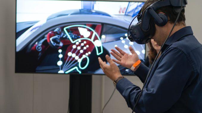 Mann steht mit VR-Brille vor dem Fernseher.