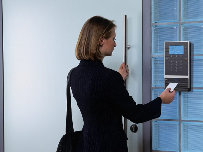 Frau steht an einer Firmentür und stempelt ein